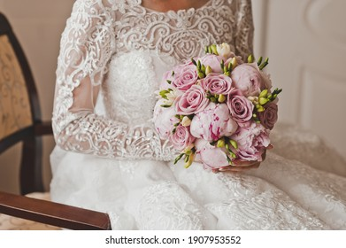A bouquet of roses and peonies in pink tones in the hands of the bride.