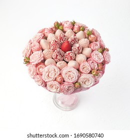 Bouquet of roses and strawberries covered with pink chocolate on a white background.