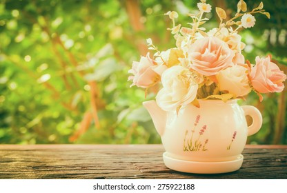 A bouquet of roses in a vase on a wooden with bokeh and tree background in the vintage style.