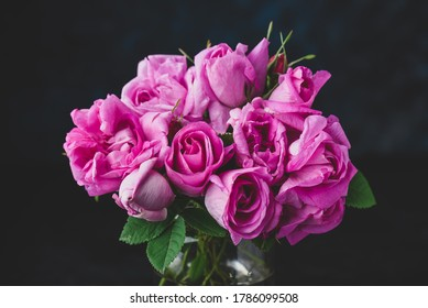 Bouquet of small pink garden roses in vase on dark background