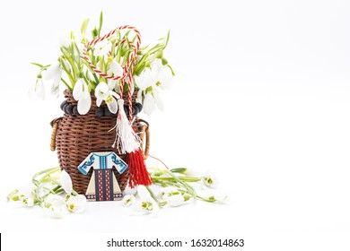 bouquet of snow drops in a basket tied with red and white string on white background and decoration first of march celebration martisor