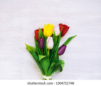 Bouquet of spring flowers. Beautiful tulips on wooden white background with copy space. Flat lay, top view.
