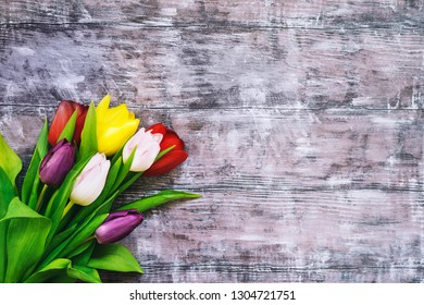 Bouquet of spring flowers. Beautiful tulips on wooden rustic background with copy space. Flat lay, top view.