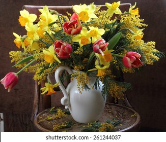 Bouquet from spring narcissuses, tulips and a yellow mimosa in a ceramic jug