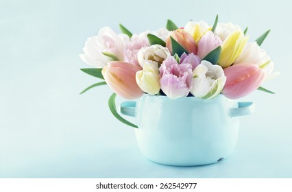Bouquet of spring tulips in a vintage vase on light blue pastel background with copy space