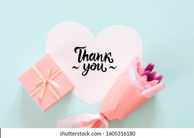 Bouquet of stabilized flowers, gift box and paper heart on blue background. Thank you lettering on paper heart