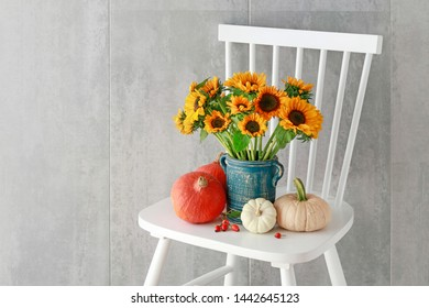 Bouquet of sunflowers and colorful pumpkins on white wooden chair.