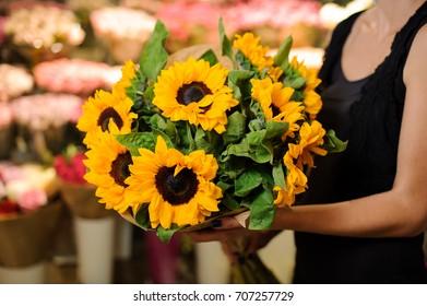 Bouquet sunflowers flower shop female florist holding. Selective focus