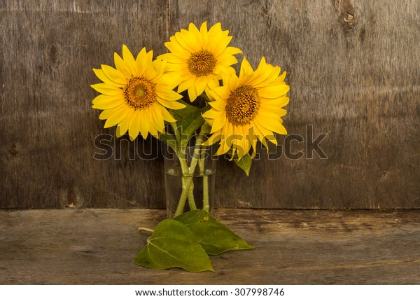 a bouquet of sunflowers in a glass on a wooden background