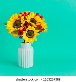 Bouquet of sunflowers and hypericum berries in mint ceramic vase, copy space. Postcard motif.