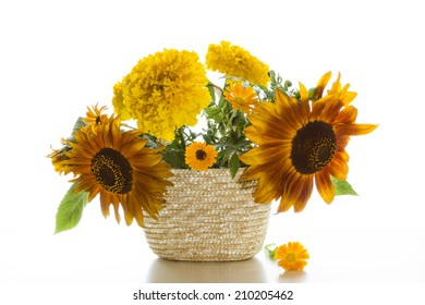 Bouquet of sunflowers and marigolds in a basket on a white background.