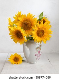 Bouquet of sunflowers in old ceramic jug against a white wooden wall.