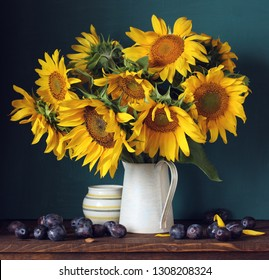 bouquet of sunflowers and plums. flowers and berries. summer still life.