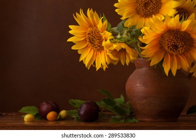 Bouquet of sunflowers and ripe cherry plums with copy space.  Fragment.  Focus on the left flower
