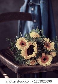 Bouquet of sunflowers and yellow roses on old wooden chair. Denim shirt on blurred background.