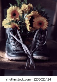 Bouquet of sunflowers and yellow roses with pair of blue boots on old wooden chair.