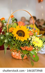 Bouquet teacher on September 1. Beginning of the school year. A bright bouquet of sunflowers, mountain ash, roses. Classroom, children in the background.