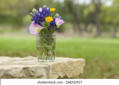 A bouquet of Texas wildflowers from the Texas Hill Country in a mason jar on a stone wall. Evening primroses, bluebonnets and yellow daisies.