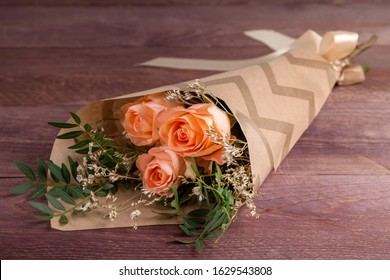 bouquet of three orange roses in Kraft paper