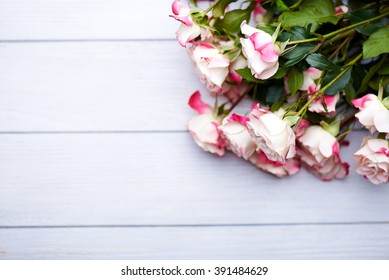 bouquet of three white and pink roses  in a glass on a blue background. With copy space.
