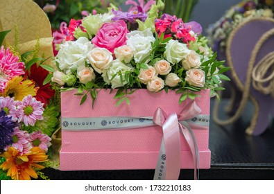 The bouquet is tied with ribbon . Multi-colored bouquet of flowers . A bouquet of flowers in a pink box.