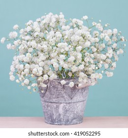 Bouquet of  tiny gypsophila (baby's-breath) flowers in vintage metal bucket