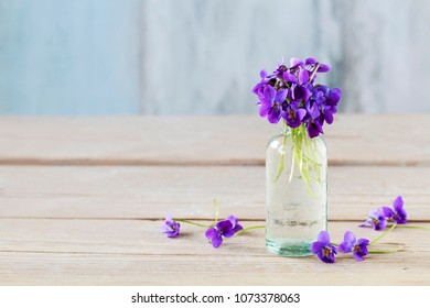 Bouquet of tiny violets (viola odorata) on wooden table, copy space.