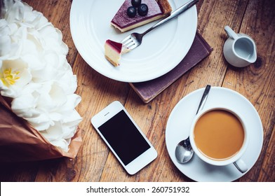 Bouquet of tulips, coffee with milk, cheesecake and smartphone on a shabby wooden floor, hipster lifestyle