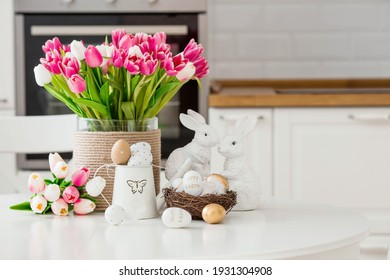 A bouquet of tulips, Easter bunnies and eggs with a golden pattern on the table. In the background is a white Scandinavian-style kitchen. Beautiful greeting card. The minimal concept. - Shutterstock ID 1931304908