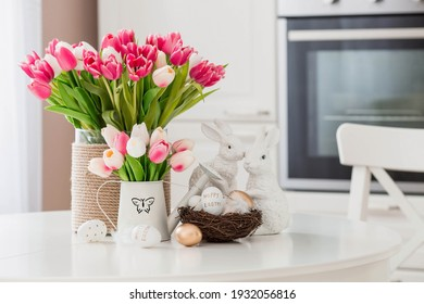 A bouquet of tulips, Easter bunnies and eggs with a golden pattern on the table. In the background is a white Scandinavian-style kitchen. Beautiful greeting card. The minimal concept. - Shutterstock ID 1932056816