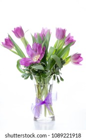 Bouquet of tulips in a glass vase against white background