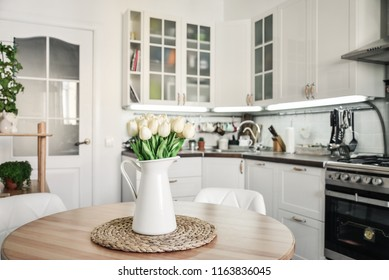 Bouquet of tulips in interior of the kitchen in Scandinavian style with white furniture and a dining table.