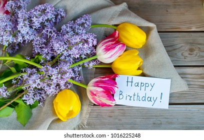 A bouquet of tulips and lilacs with an inscription happy birthday on a wooden background. Festive postcard. Decorative, spring concept.