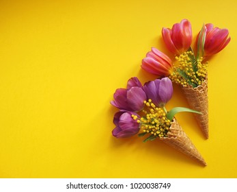 Bouquet of tulips and mimosa flowers on yellow background