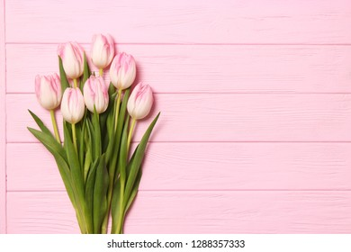 A bouquet of tulips on a wooden background top view. Spring background. Background to Mother's Day, International Women's Day, birthday.