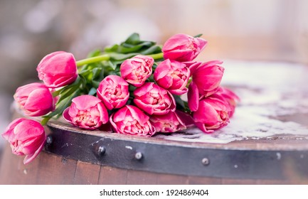 Bouquet of tulips on a wooden barrel. An armful of pink flowers lie on the table. Spring concept. Copy space. Composition for Women's Day March 8, Mother's Day.