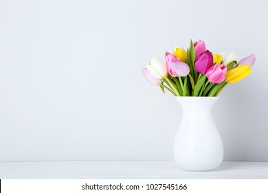 Bouquet of tulips in vase on wooden table