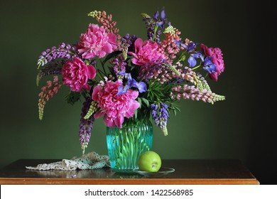 bouquet in a vase, lupins and peonies. still life with garden flowers and Apple.