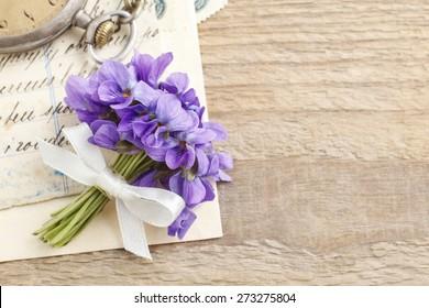 Bouquet of violet flowers (viola odorata) and vintage letters, copy space