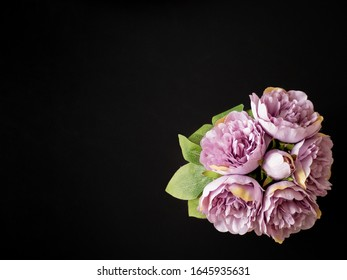 Bouquet of violet peonies in a vase on a black background. Bridal floral theme. Wedding or baptism invitation idea. Top view. Flat lay. Minimalism.