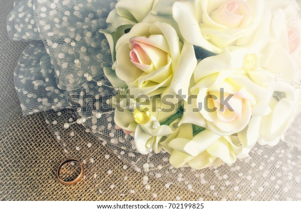 Bouquet and wedding ring of the bride on burlap. The bouquet is issued by jewelry. In style a vintage. Vignette light. Indoors. Horizontal format. Color. Photo.