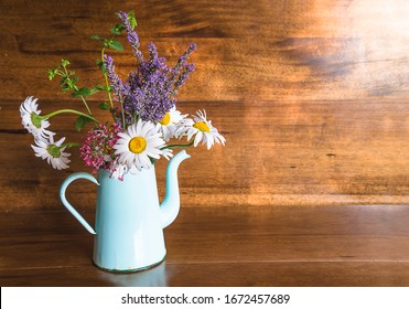 Bouquet of white daisies, blue lavenders and valerian flowers in old coffee pot on beautiful vintage wooden background with sunrays