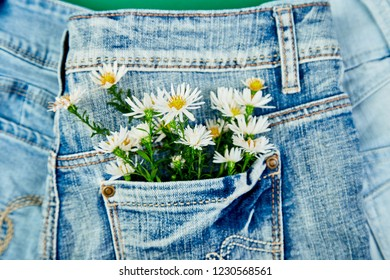 Bouquet of white flower in the pocket of a jeans on green background. Minimalis. Denim concept. Flat lay. Copy space. Creative layout for spring festive theme.