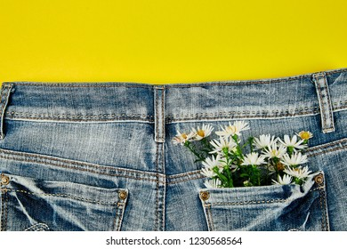Bouquet of white flower in the pocket of a jeans on yellow background. Minimalis. Denim concept. Flat lay. Copy space. Creative layout for spring festive theme.