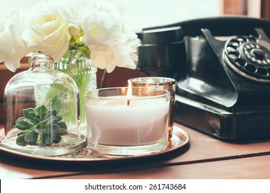 Bouquet of white flowers in a vase, candles on a copper vintage tray, old rotary phone, retro home decor