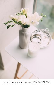 Bouquet of white freesias in vase and aromatic candle on table