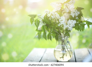Bouquet of white lilac in a vase on a wooden table