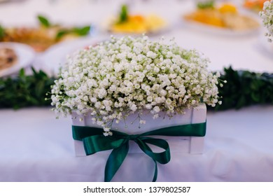 bouquet of white lily of the valley in a beautiful vase on the wedding table