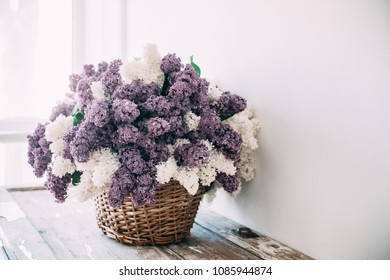 Bouquet of white and purple lilac flowers in wicker basket on ta