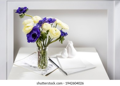 Bouquet of white ranunculus and blue anemone in the vase on a white coffee table near fake fireplace. The books and journal. Shadow.